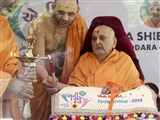 Swamishri lighting the inaugural lamp (deep-pragatya) at the start of the Yuva Shibir-2015, Vadodara and Bharuch, 'My Role Model - Eni Reetey Reet'