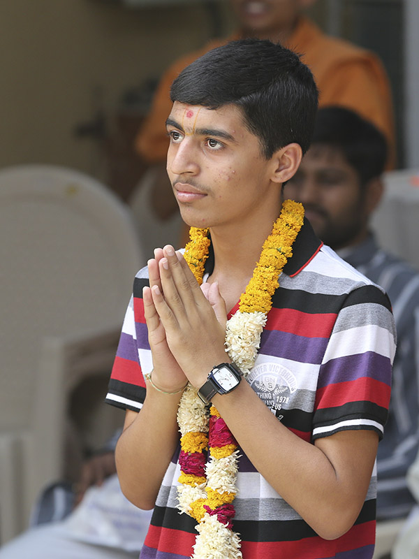 Dharmik Parmar, a student of Swaminarayan Vidyamandir, Sarangpur, who stood first in the SSC State Board (Standard 10) exams in the 99.99 percentile, doing darshan of Swamishri