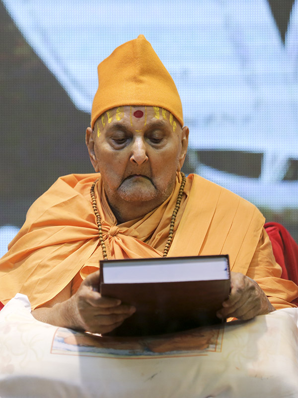 Swamishri sanctifies a reprint of the four Ph.D. theses written by senior sadhus in Yogiji Maharaj's time