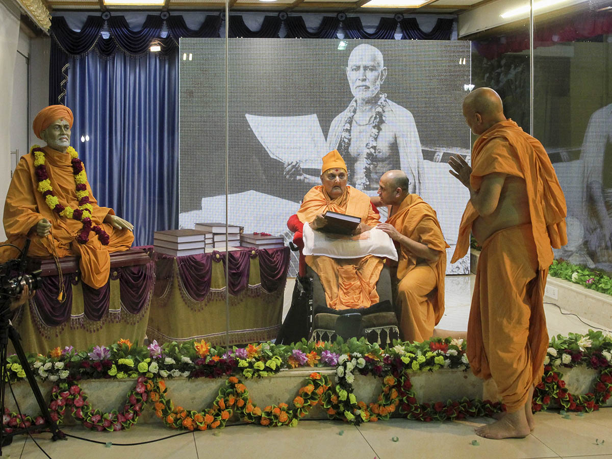 Swamishri blesses Pujya Viveksagar Swami after sanctifying his Ph.D. thesis