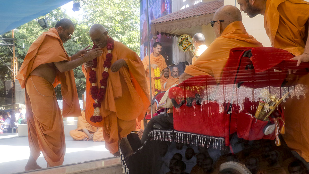 Pujya Doctor Swami is honored with a garland