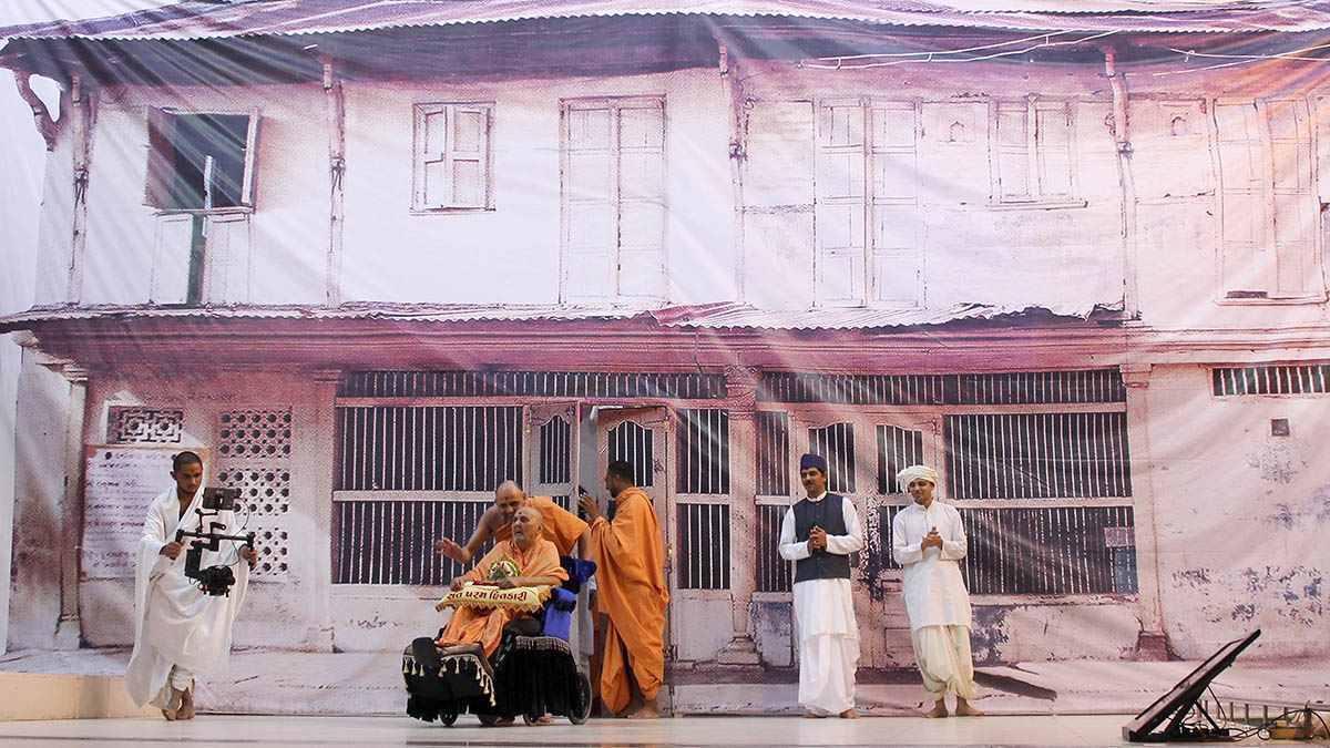 Swamishri arrives in the mandir grounds (Swamishri's birth home in background)