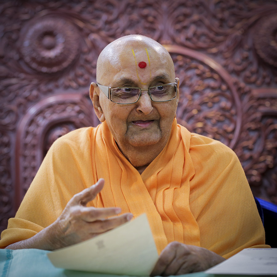 Swamishri in a divine, jovial mood while reading a letter