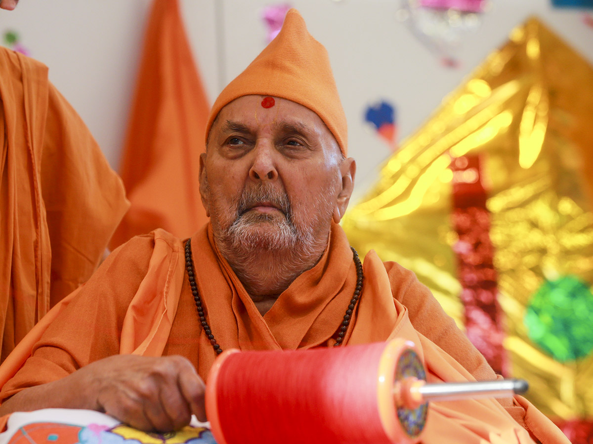 Swamishri holds the string of a kite in his hands
