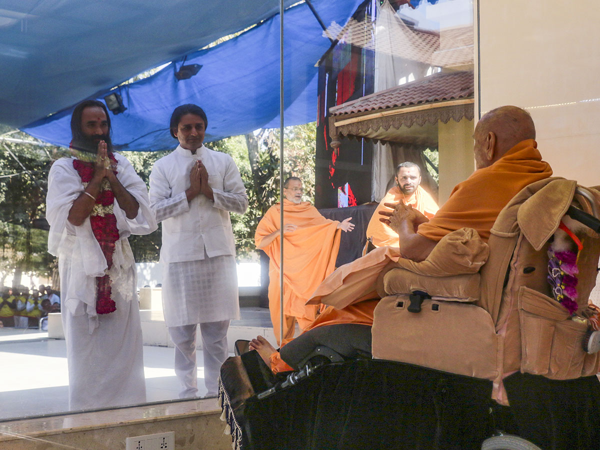 Swami Dayanandji of the Art of Living Foundation is honored with a garland in the presence of Swamishri