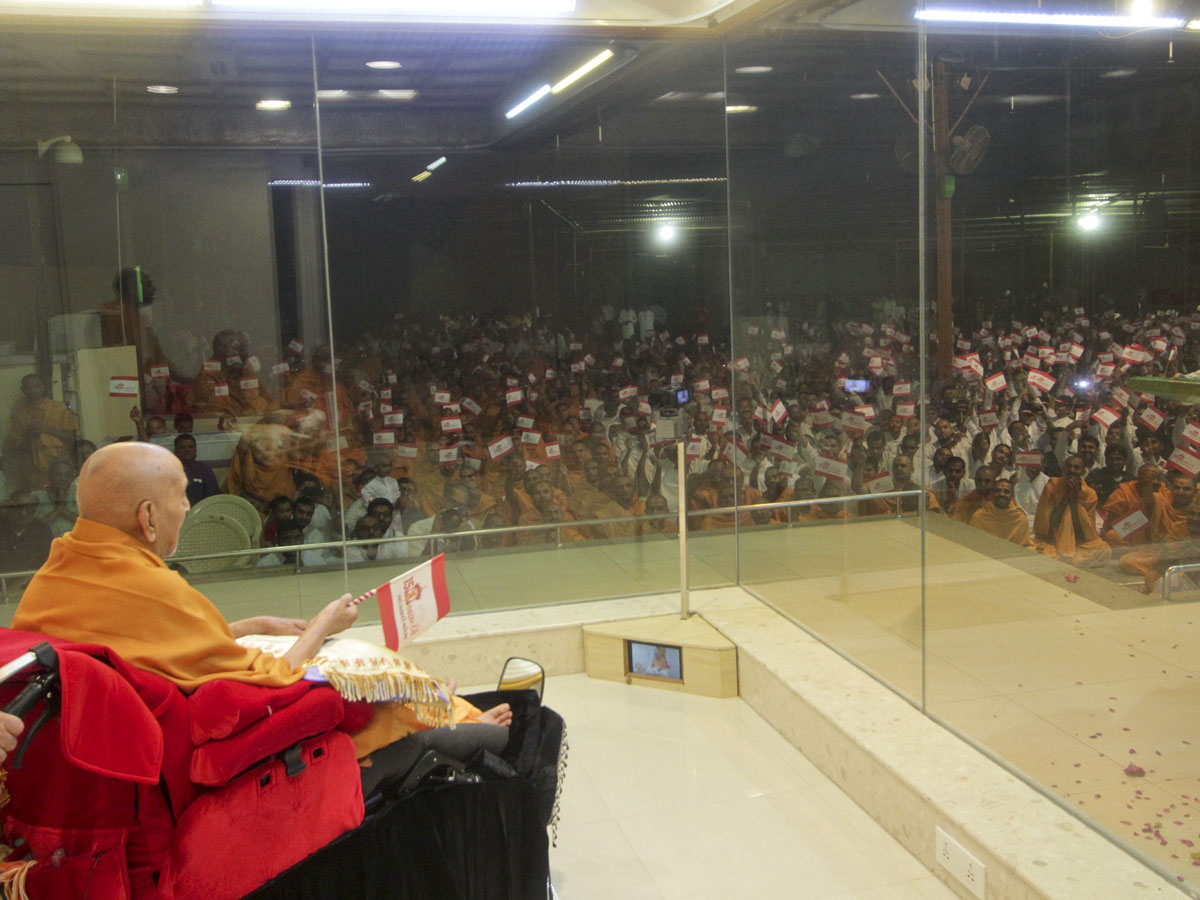 Swamishri waves a celebration flag