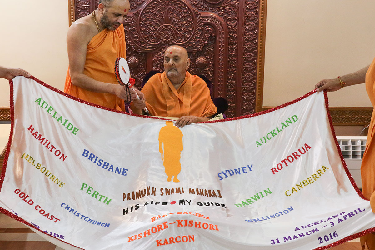 Swamishri is honored with a shawl from Australia and New Zealand