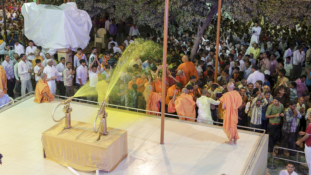 Devotees enjoy the celebrations with sanctified colored water