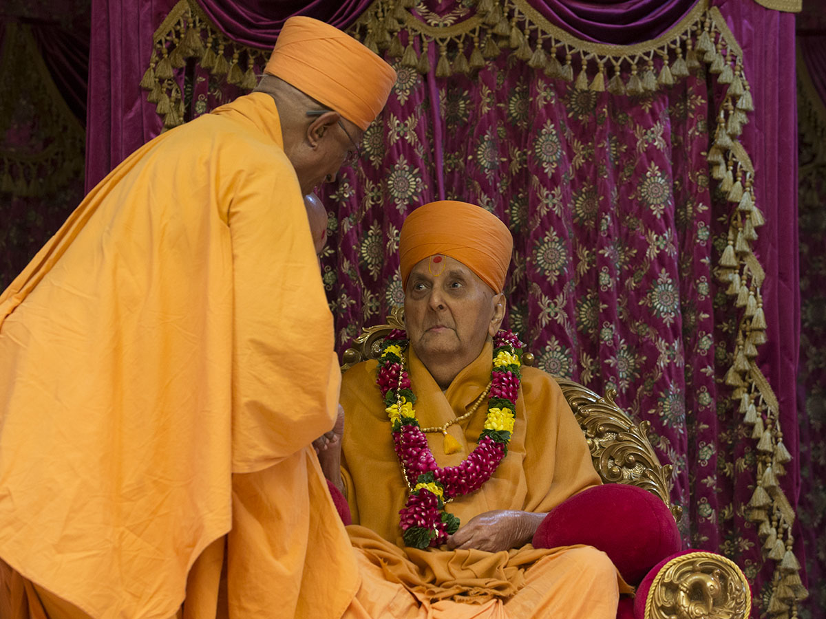 Pujya Doctor Swami honors Swamishri with a garland