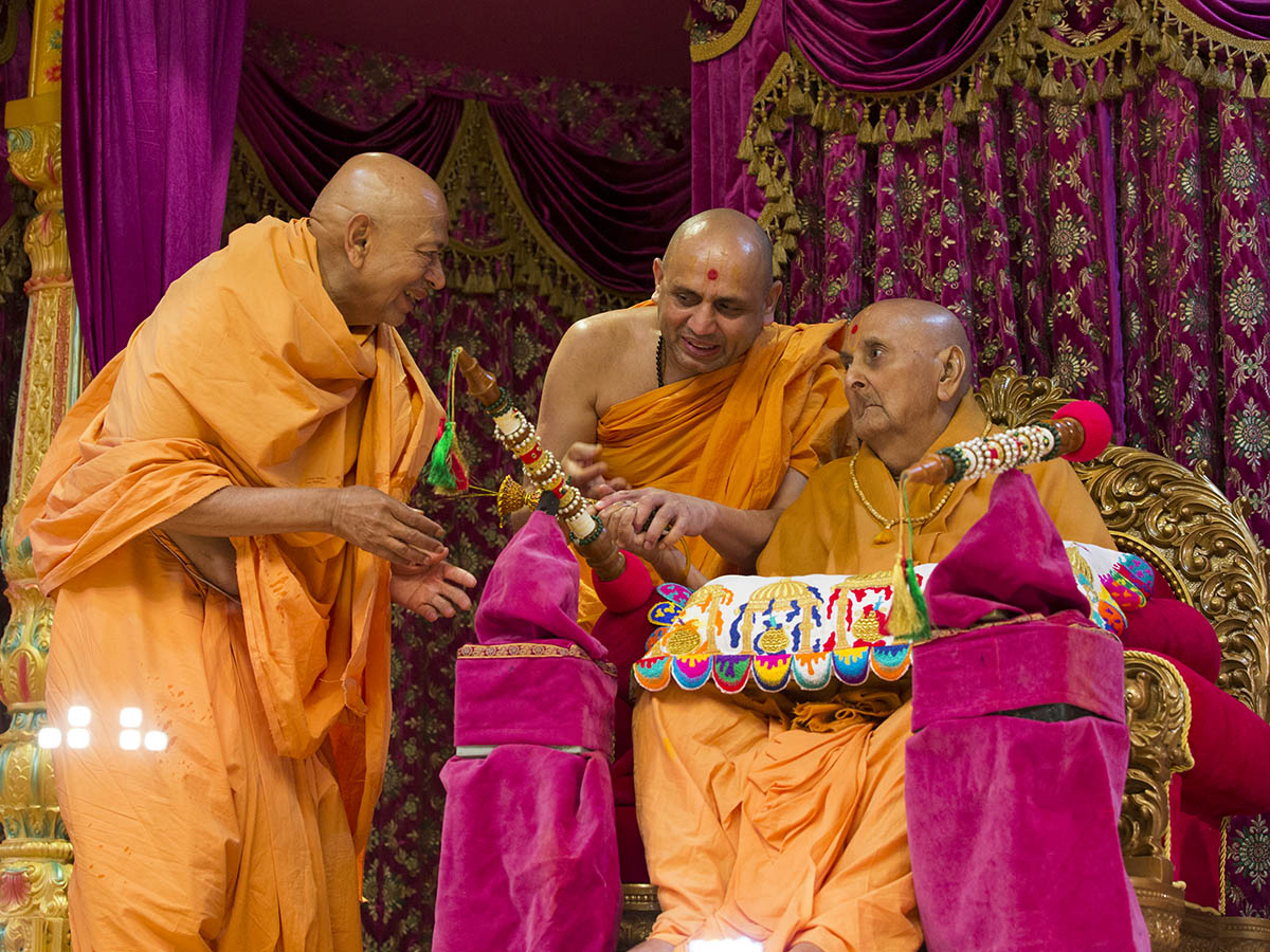 Swamishri showers sanctified colored water on Pujya Tyagvallabh Swami