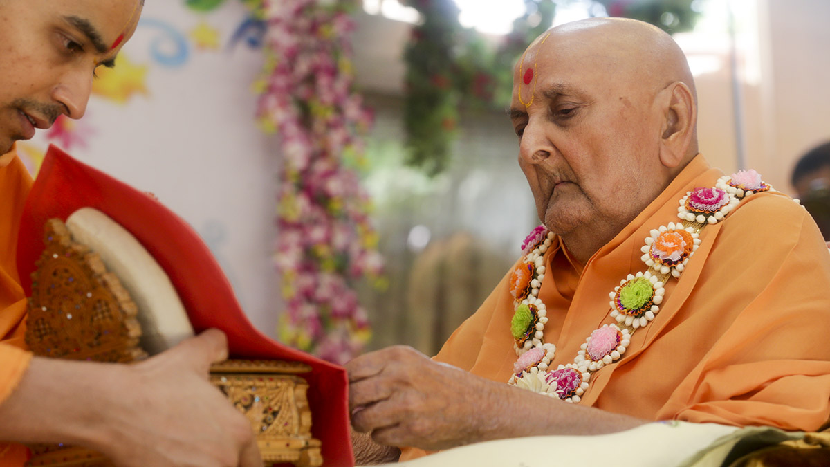 Swamishri engrossed in darshan of Shri Harikrishna Maharaj in the morning