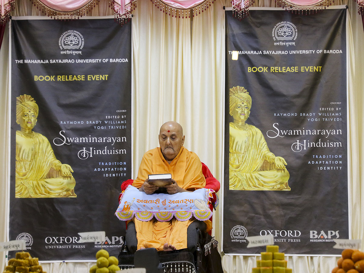 Swamishri sanctifies an Oxford University Press print publication, 'Swaminarayan Hinduism: Tradition, Adaptation, Identity'