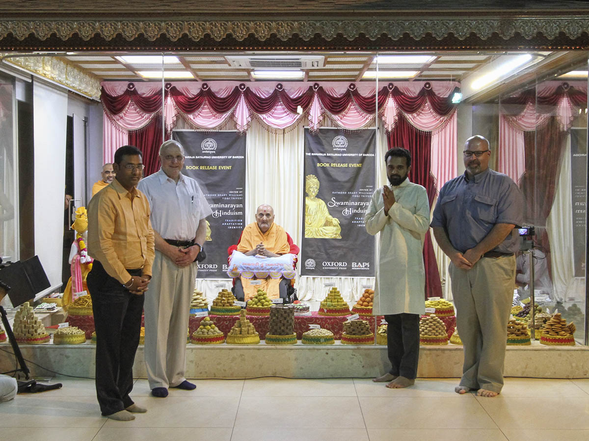 Prof. Raymond Brady Williams, Prof. Yogi Trivedi,  Pastor Matthew Manning and Nitesh Dave offer the book to Swamishri
