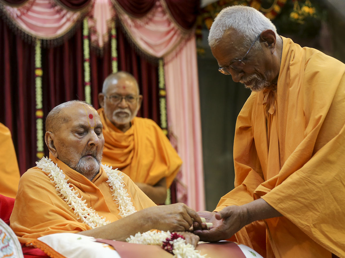 Swamishri gives prasad to Pujya Doctor Swami