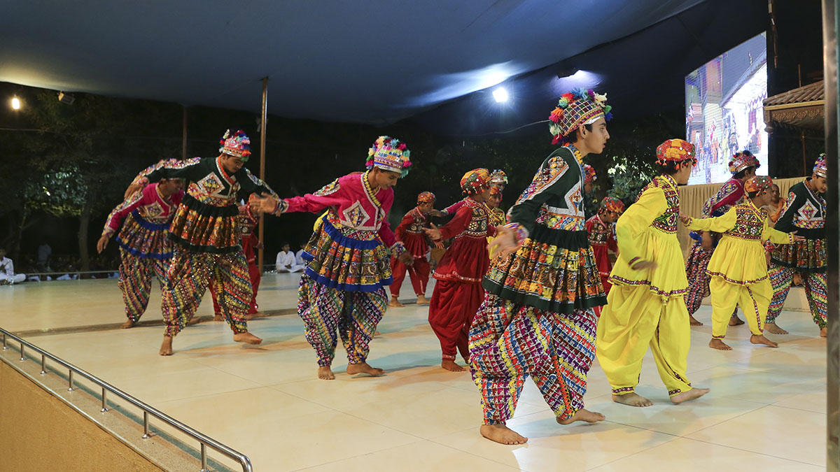 Children from Navsari perform a cultural dance before Swamishri