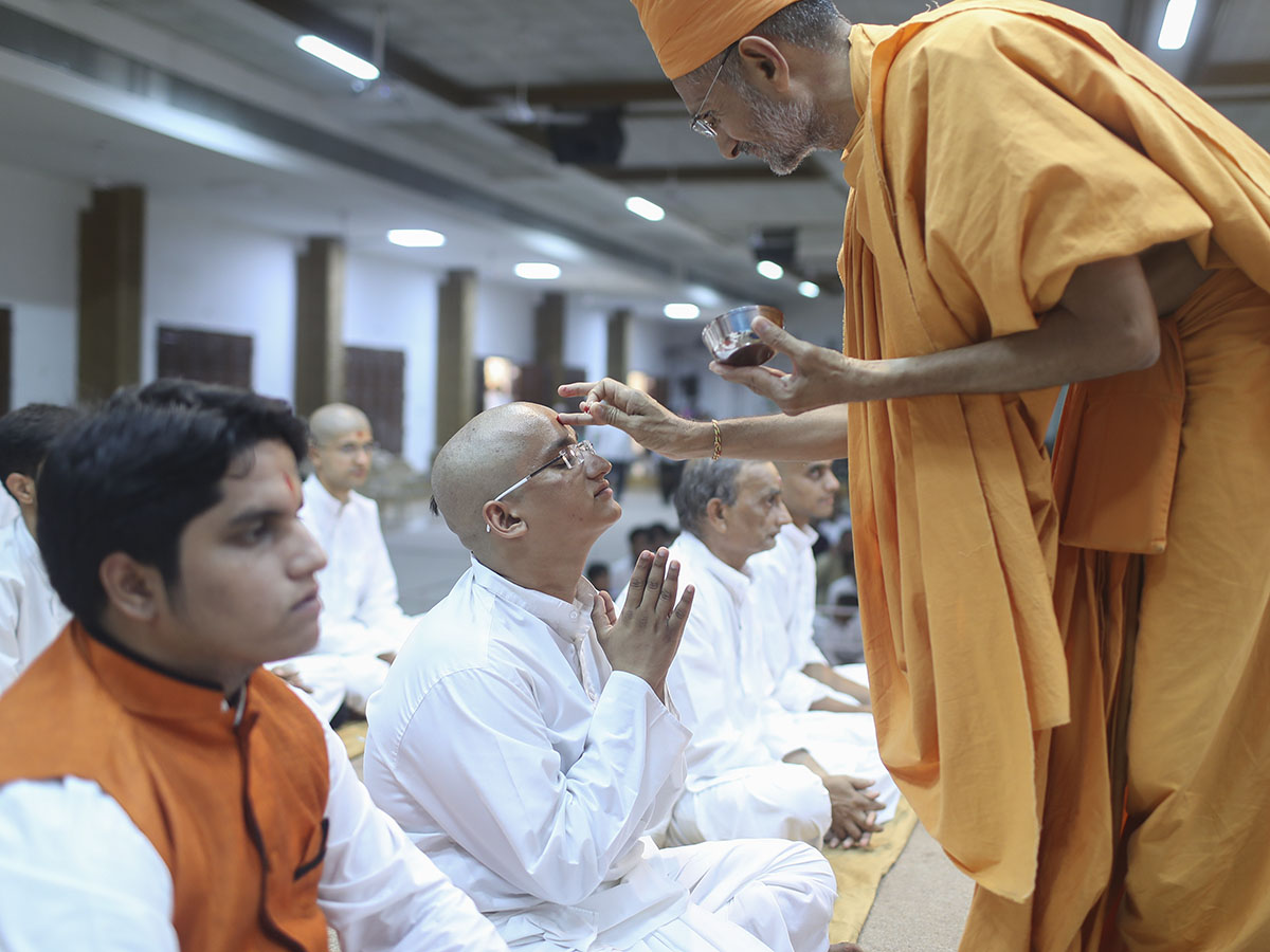 Sadhaks and their fathers engaged in mahapuja rituals before being initiated as parshads