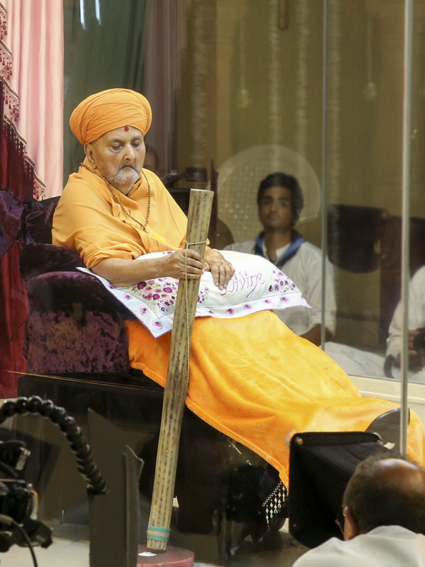 Swamishri with a wooden stick, recounting his seva of flattening the mud floor in Sarangpur just after his diksha.