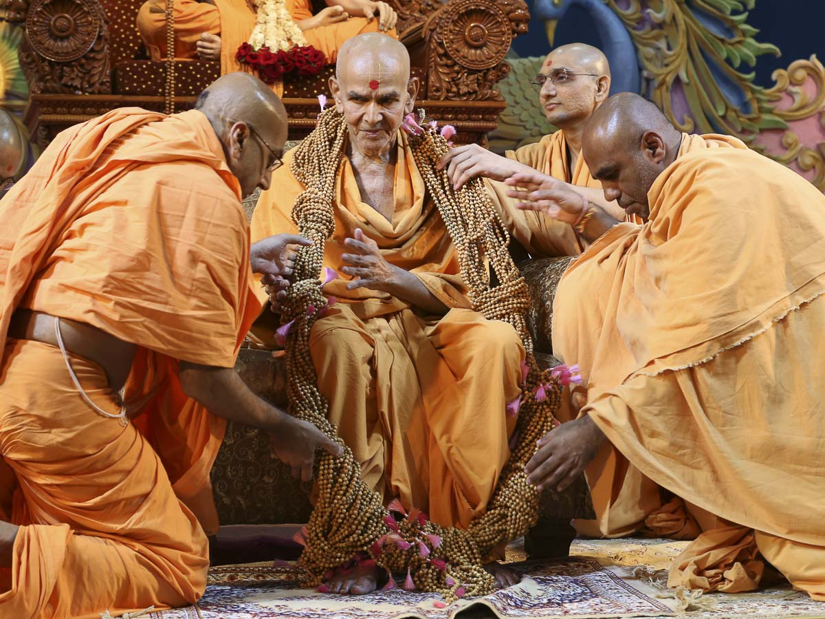 Sadhus honor Param Pujya Mahant Swami with a garland, 21 Aug 2016