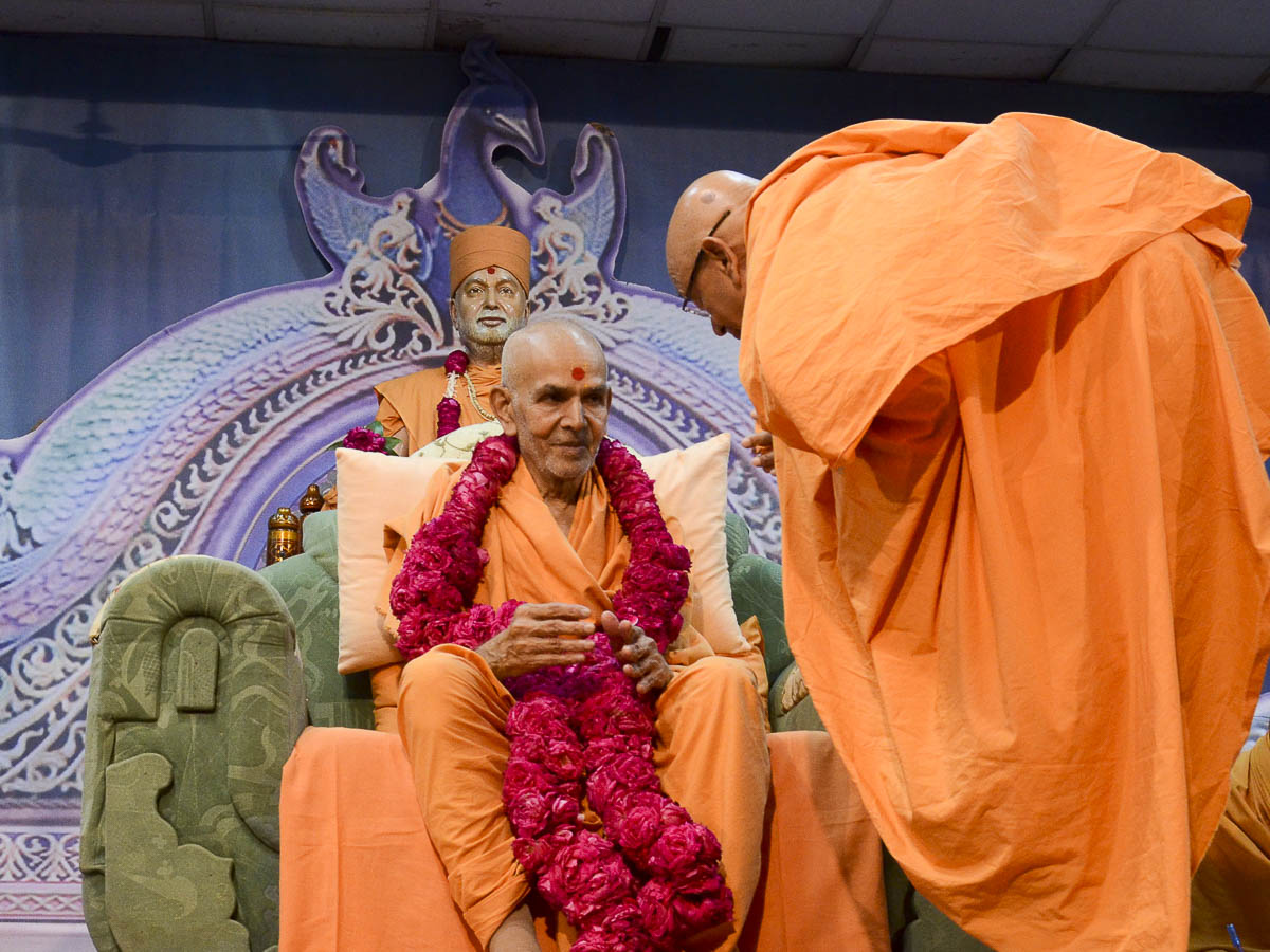 Pujya Tyagvallabh Swami honors Param Pujya Mahant Swami with a garland, 24 Aug 2016