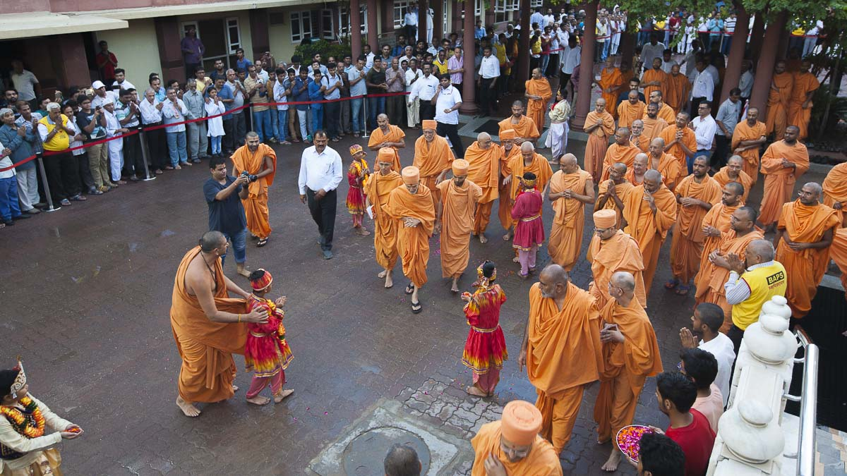 Children welcome HH Mahant Swami Maharaj with flower petals, 29 Aug 2016