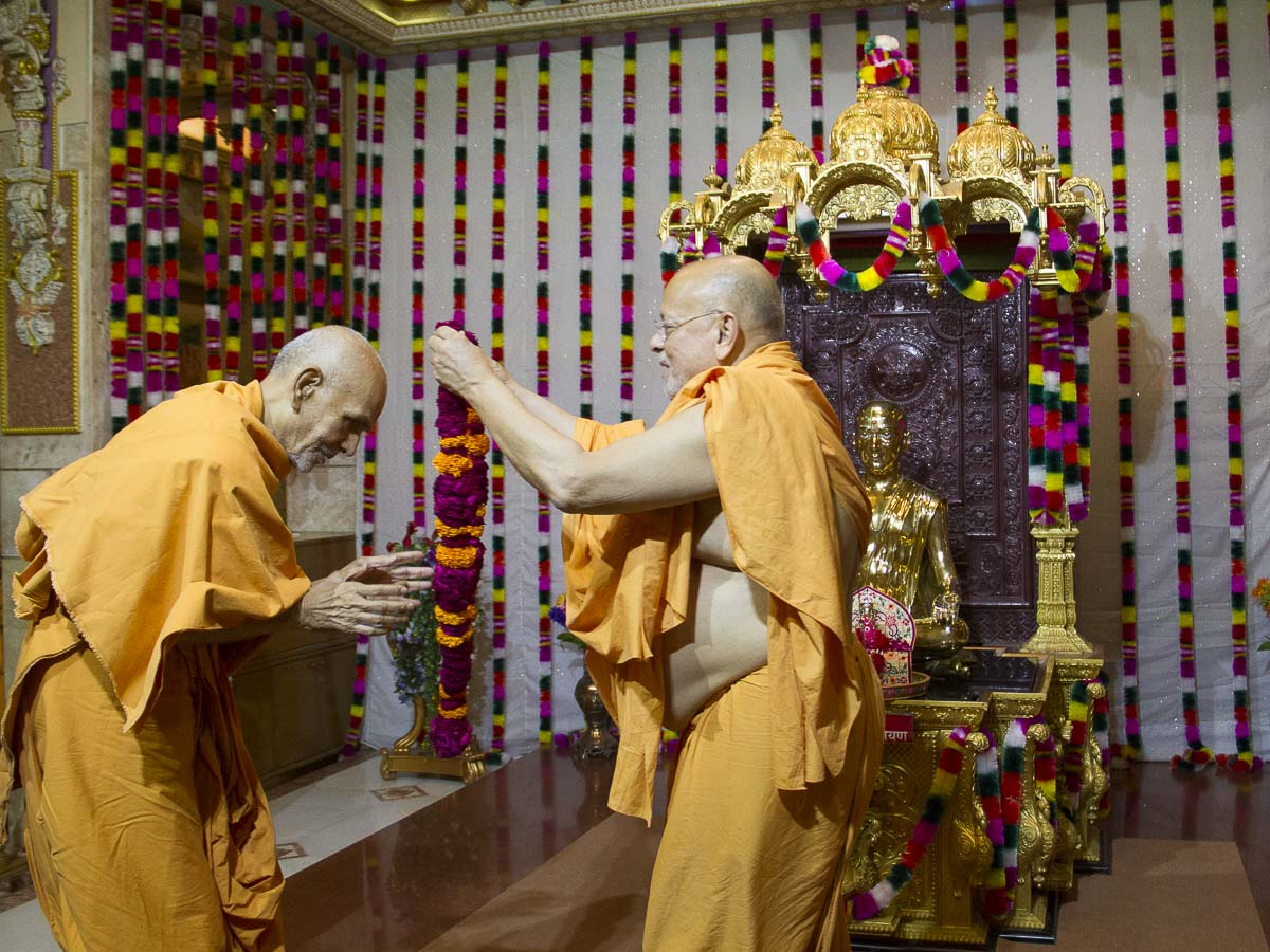 Pujya Ishwarcharan Swami welcomes Param Pujya Mahant Swami with a garland, 29 Aug 2016