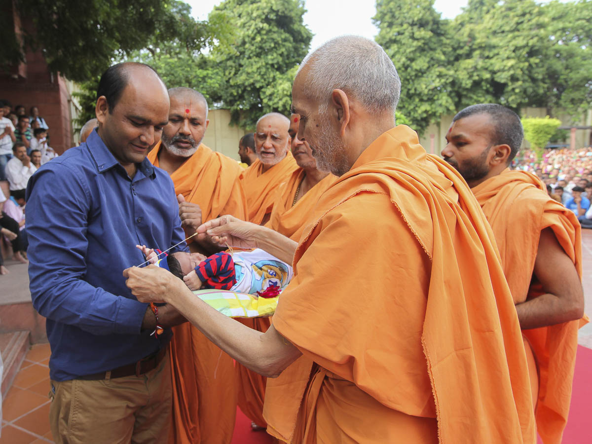 Param Pujya Mahant Swami gives vertman to a child, 3 Sept 2016