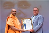 San Bernardino County Supervisor, Curt Hagman, gifting a copy of San Bernardino's resolution in memory of HH Pramukh Swami Maharaj