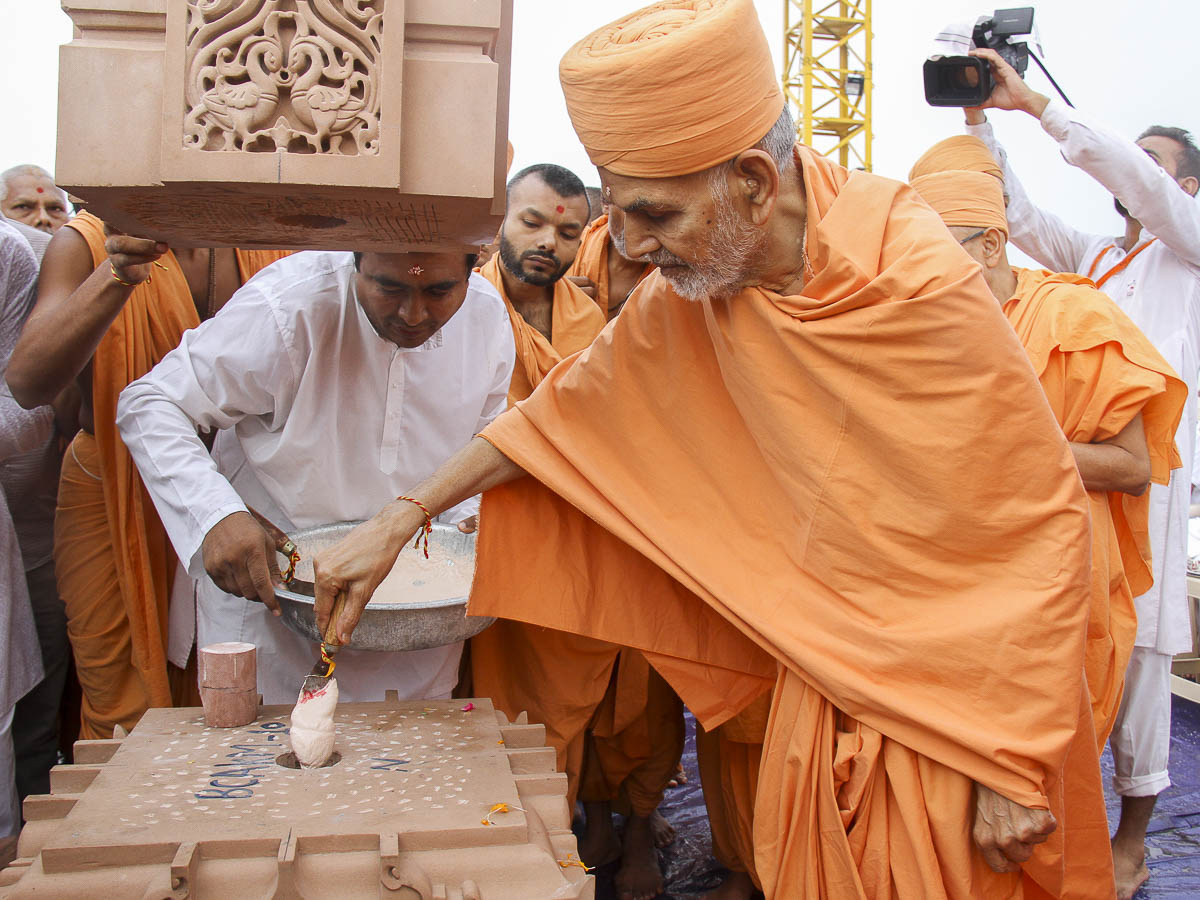 Param Pujya Mahant Swami fills the pillar with a special adhesive mixture, 6 Oct 2016