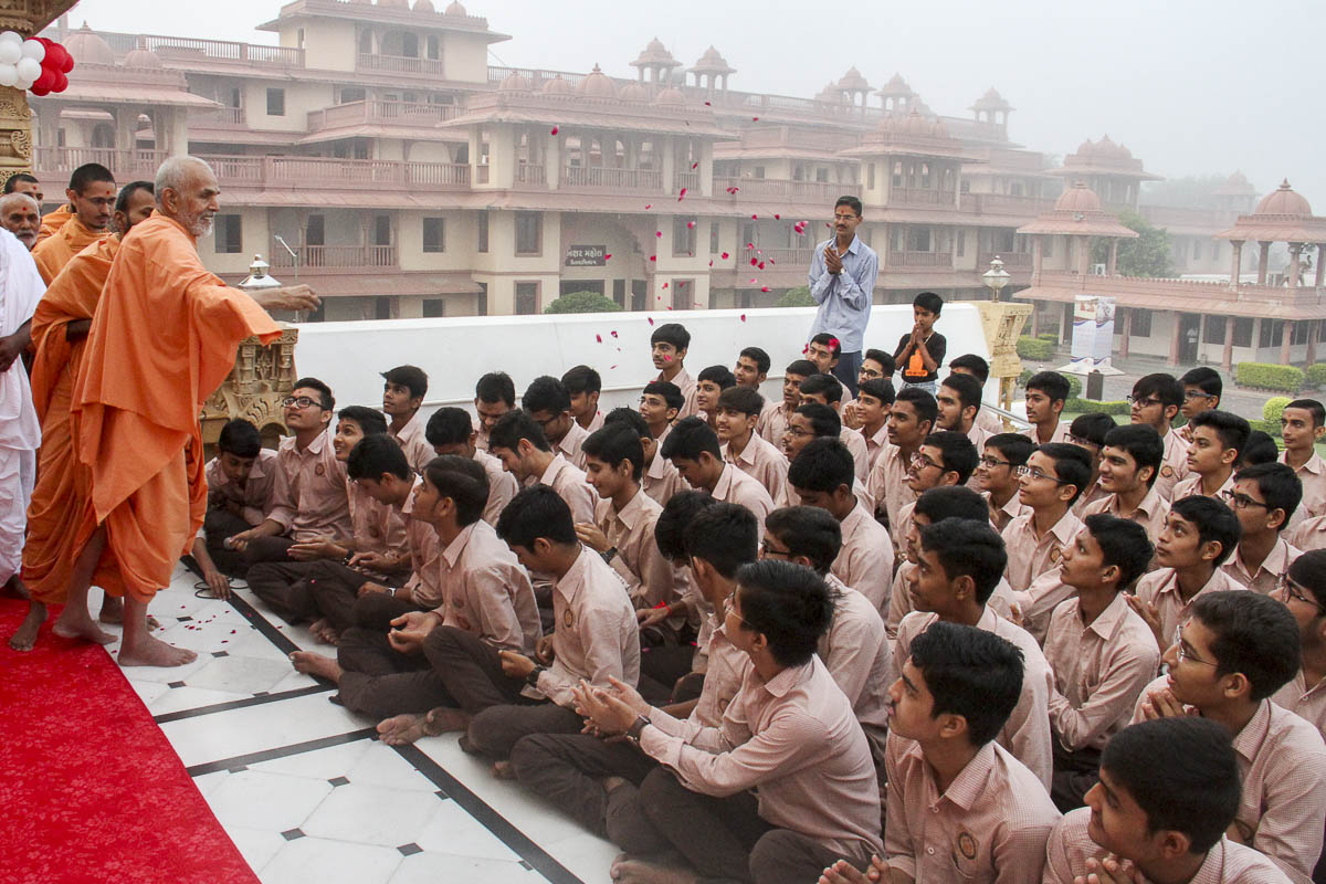 Param Pujya Mahant Swami blesses students of Swaminarayan Vidyamandir by showering flower petals, 13 Oct 2016