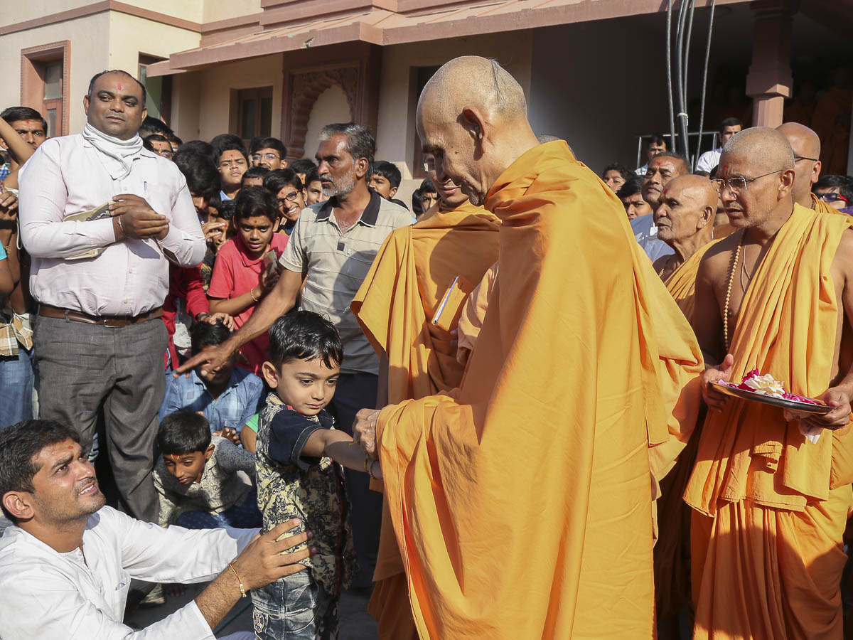 Param Pujya Mahant Swami ties nadachhadi on a child's wrist, 16 Oct 2016