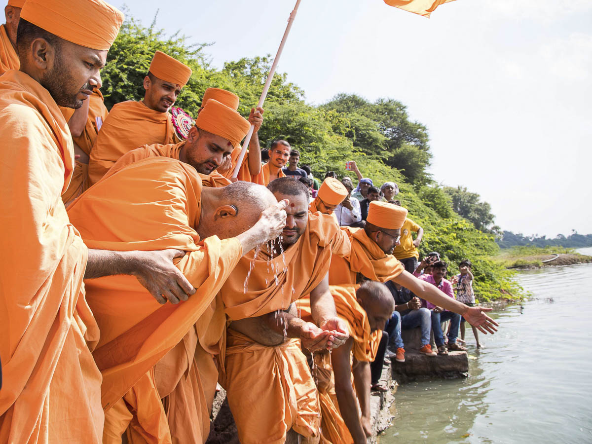 Param Pujya Mahant Swami applies the sanctified water of River Und to his head, 23 Oct 2016