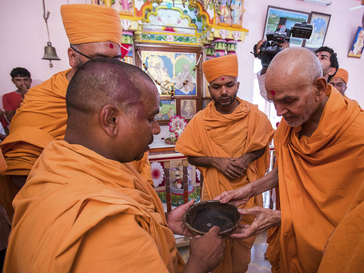 Param Pujya Mahant Swami engaged in darshan of a bowl sanctified by Bhagwan Swaminarayan, 23 Oct 2016