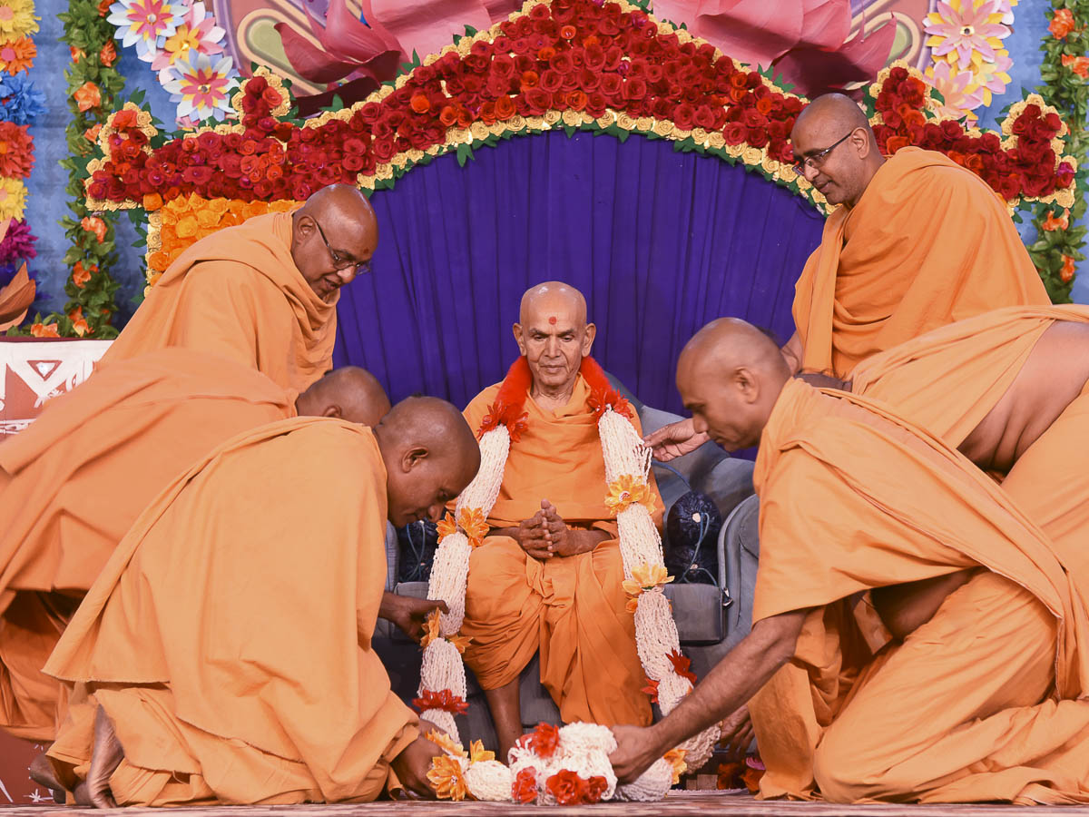 Sadhus honor Param Pujya Mahant Swami Maharaj with a garland, 13 Dec 2016