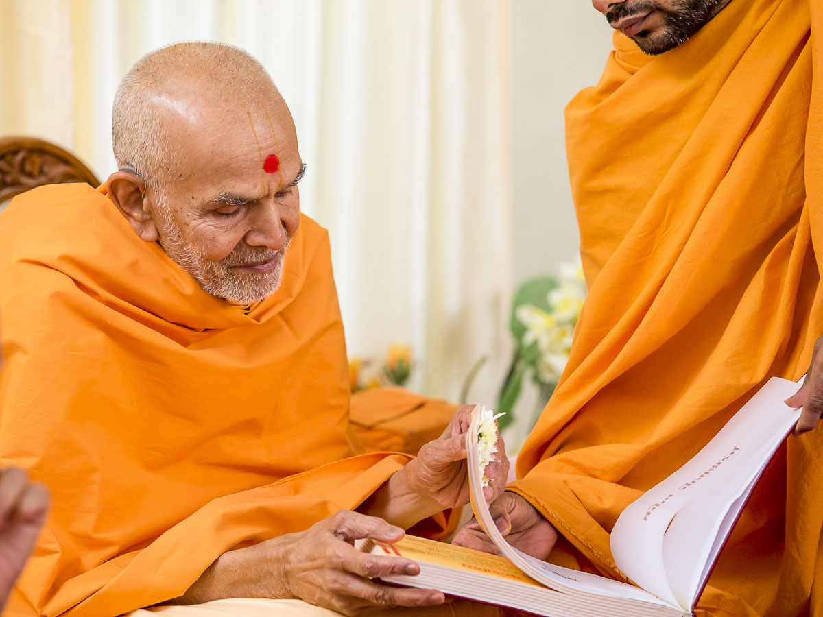 Param Pujya Mahant Swami Maharaj sanctifies a book, 24 Dec 2016