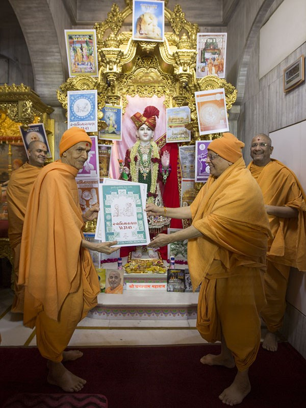 Param Pujya Mahant Swami Maharaj sanctifies photos of title pages of past Swaminarayan Prakash issues, 13 Jan 2017