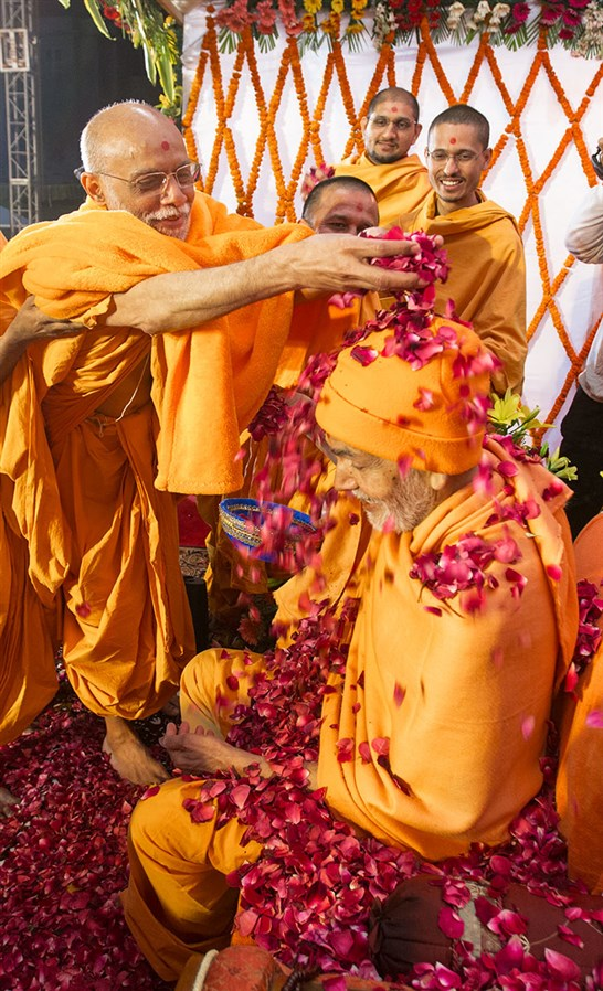 Bhaktinandan Swami showers flower petals on Param Pujya Mahant Swami Maharaj, 3 March 2017