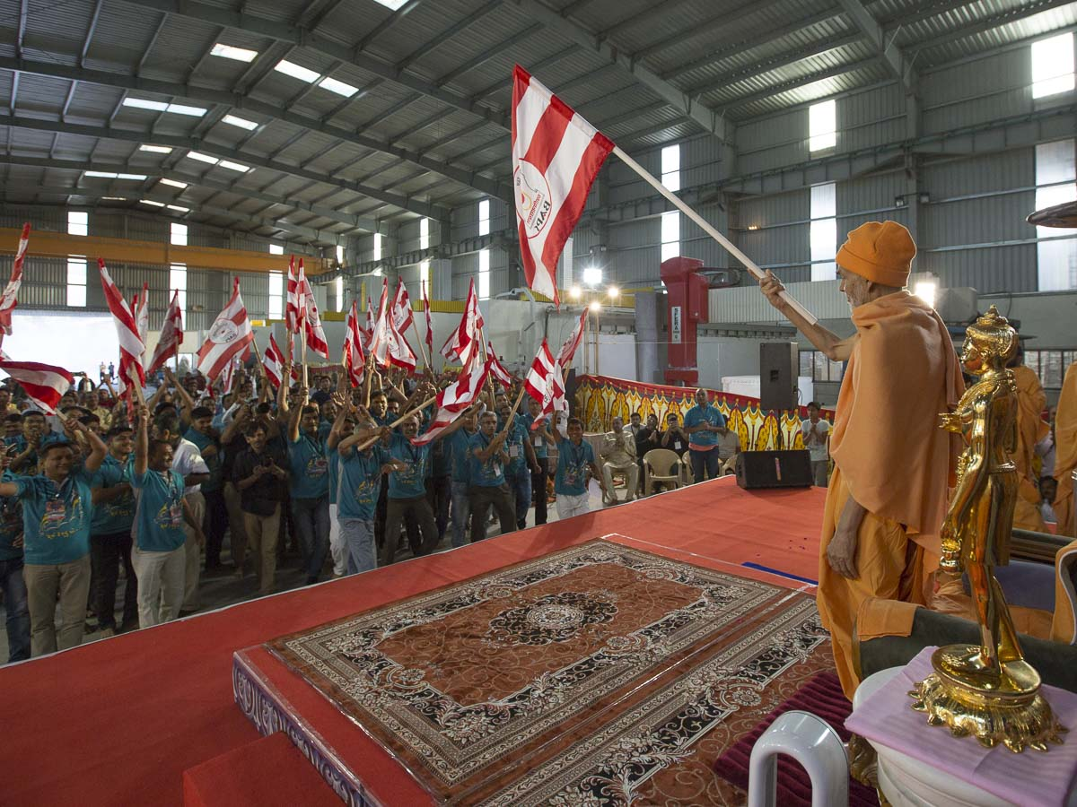 Param Pujya Mahant Swami Maharaj and volunteers wave BAPS flags, 6 Mar 2017