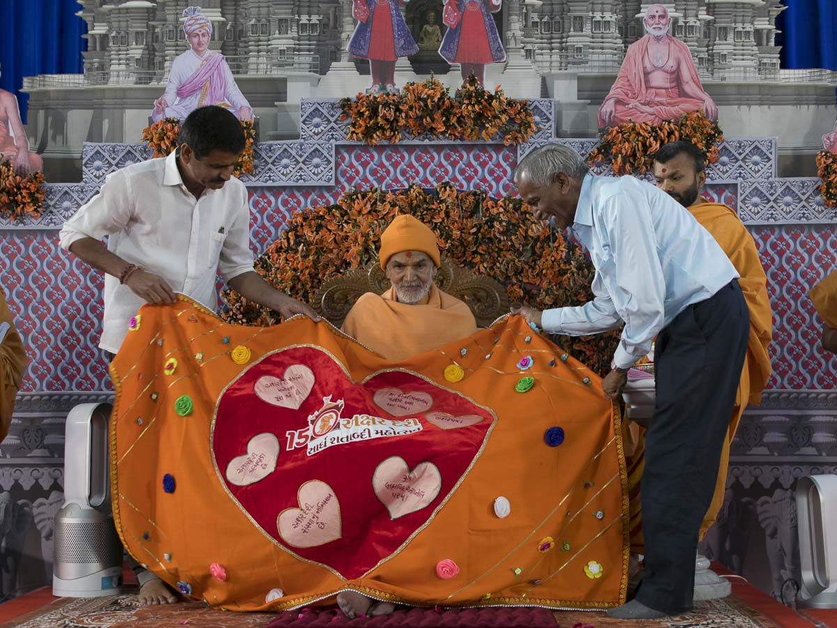 Harshadbhai and Prakashbhai honor Param Pujya Mahant Swami Maharaj with a shawl, 7 Mar 2017
