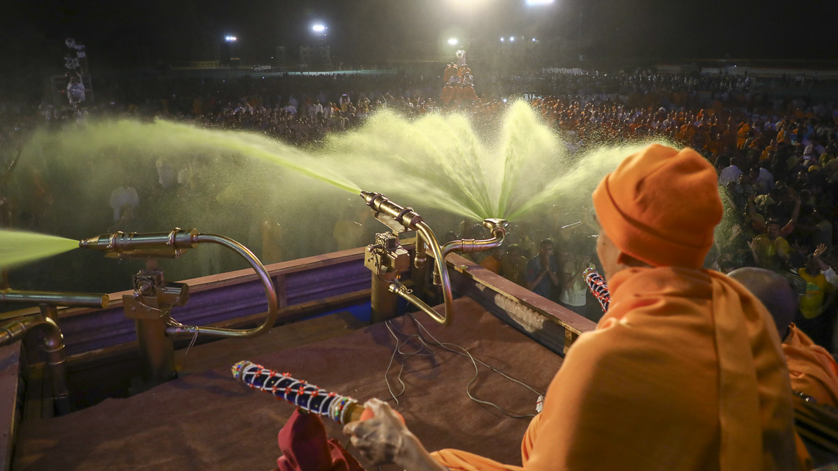 Param Pujya Mahant Swami Maharaj showers sanctified saffron-scented water on volunteers, 11 March 2017