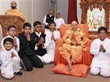Children welcome Pujya Tyagvallabh Swami with a garland