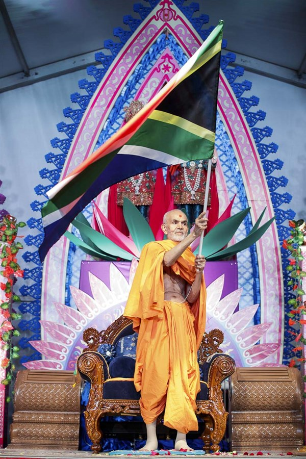 Param Pujya Mahant Swami Maharaj waves a South African flag, 28 Mar 2017