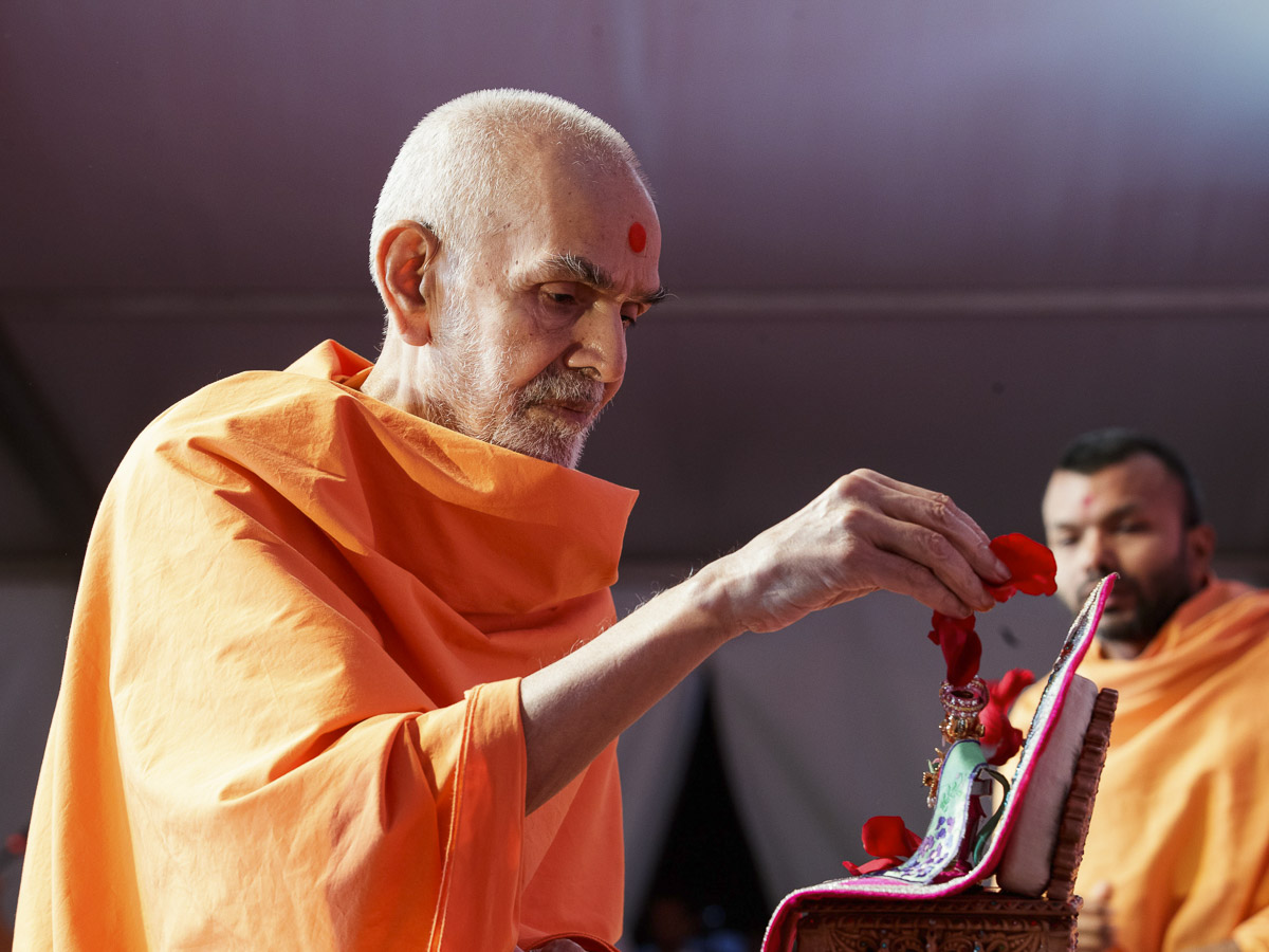Swamishri showers flower petals on Shri Harikrishna Maharaj in the symbolic Pushpadolotsav celebration assembly, 28 Mar 2017