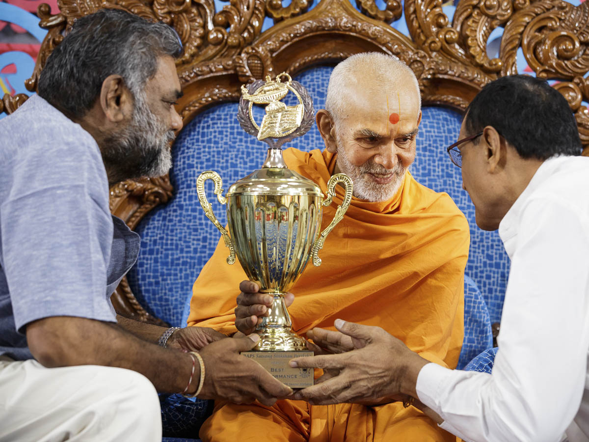 Swamishri presents a Satsang Exam award to a devotee, 30 March 2017