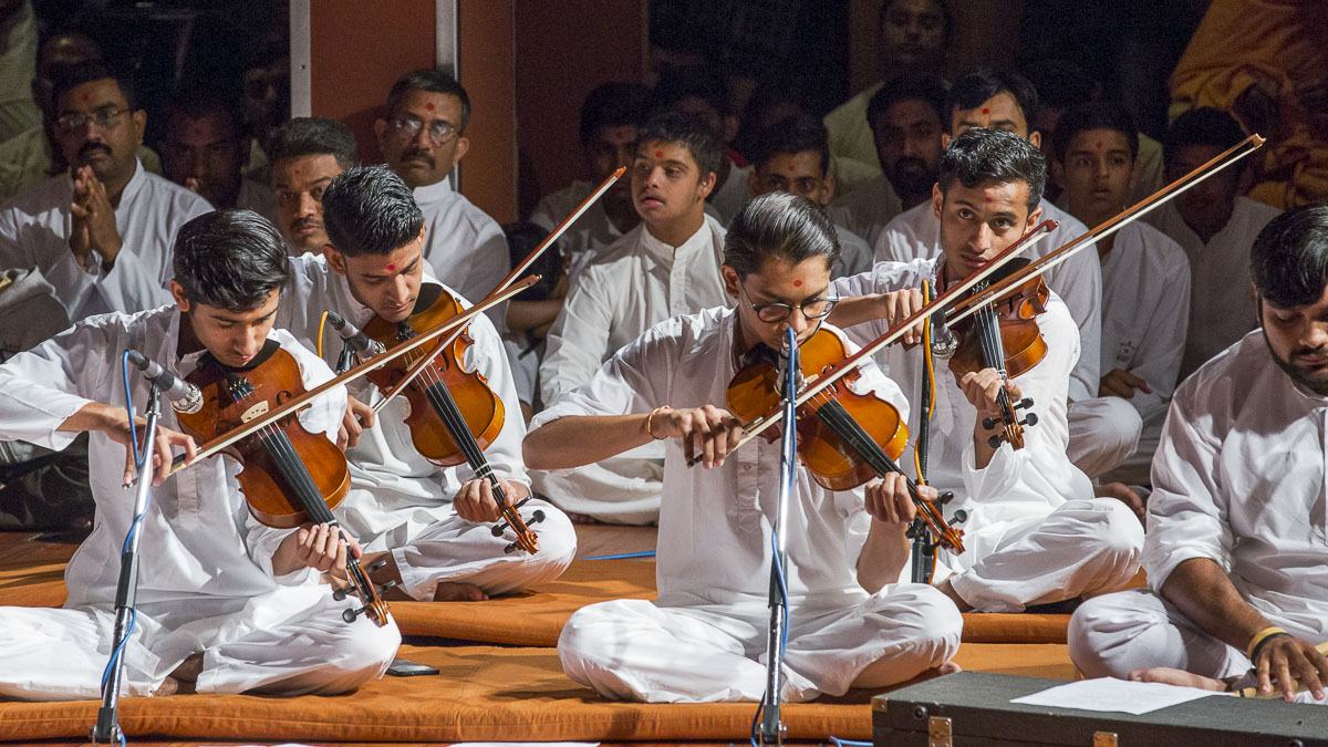 Youths play violins in Swamishri's morning puja, 14 Apr 2017