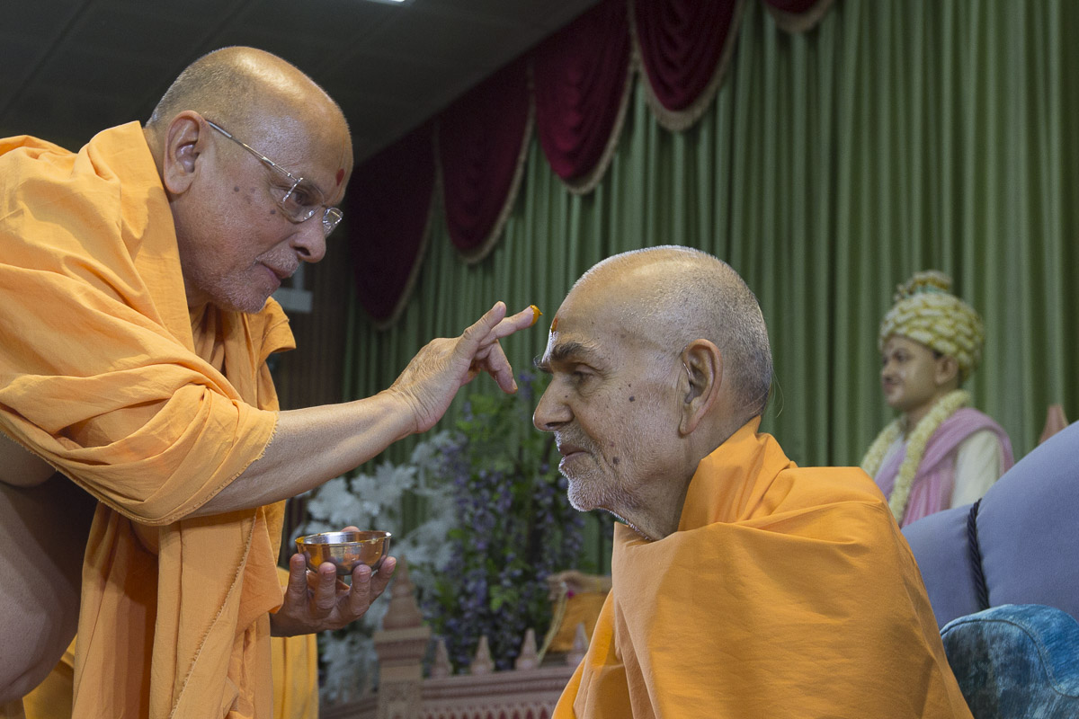Pujya Ishwarcharan Swami applies chandlo to Swamishri, 16 Apr 2017