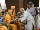 HH Mahant Swami Maharaj presents books to invited guests