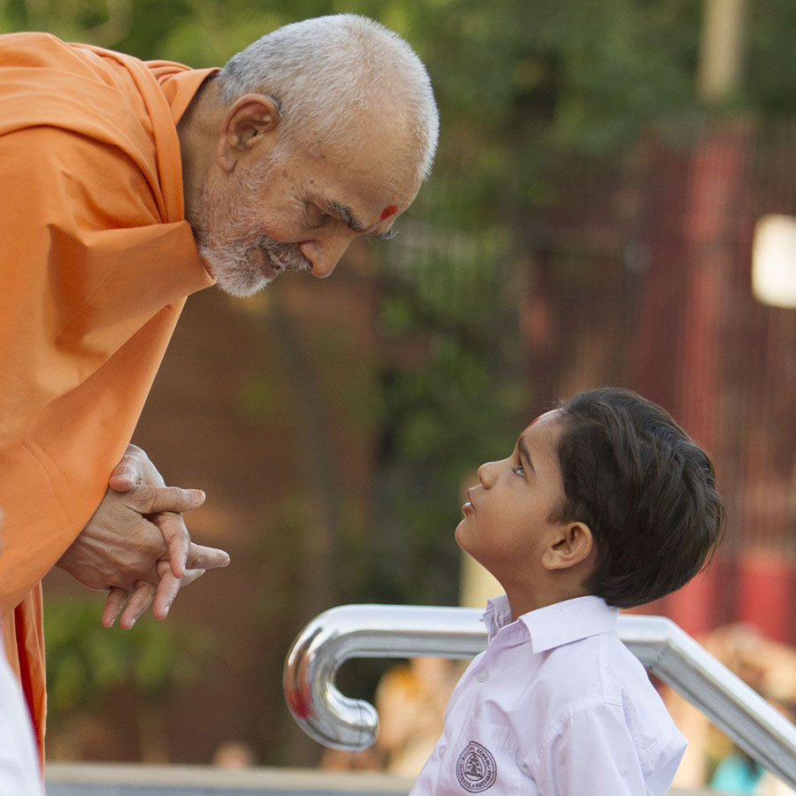 Swamishri interacts with a child, 4 May 2017