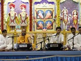 A sadhu and youths sing kirtans