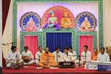 A sadhu and youths sing kirtans during the kirtan aradhana assembly