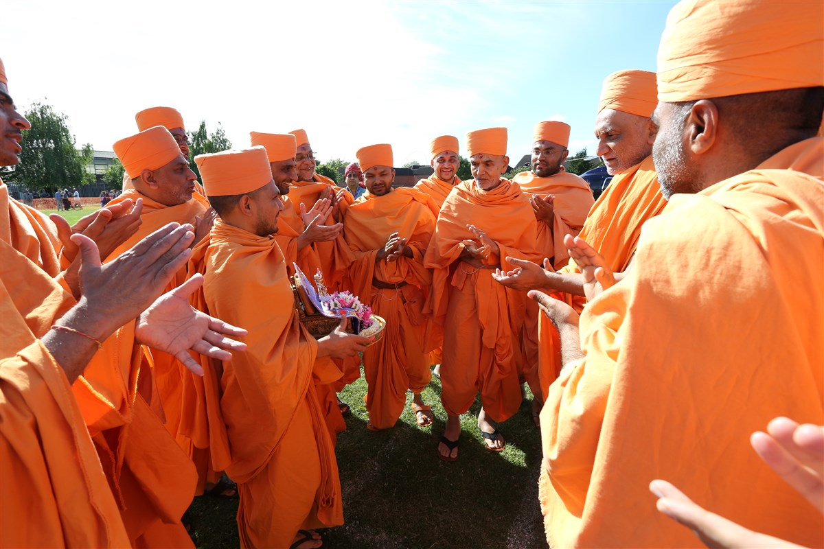 Swamishri performs dhun with sadhus upon arrival at Gibbons Recreation Ground